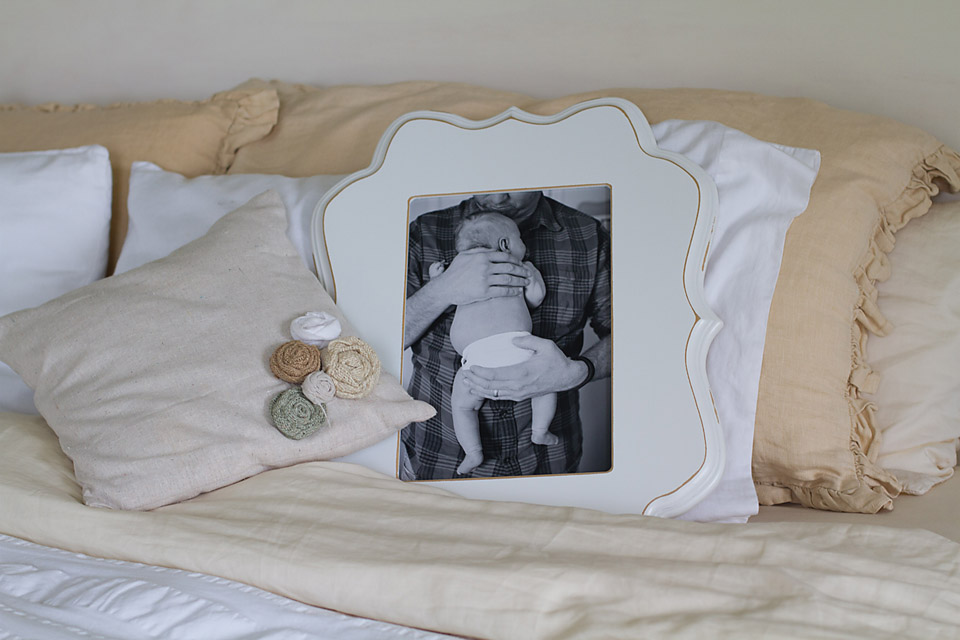 Organic Bloom frame in white staged on bed among pillows with newborn baby portrait
