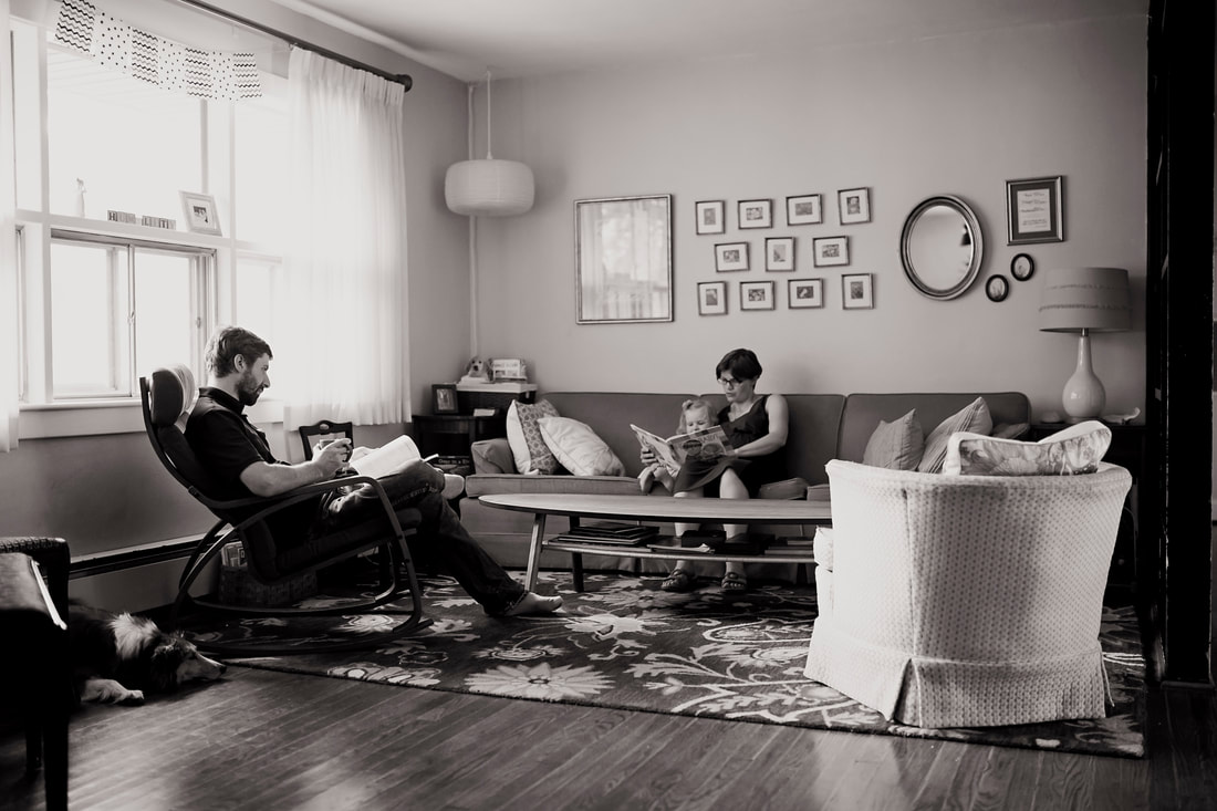 black and white image of family quietly reading in their living room with dog sleeping on the floor