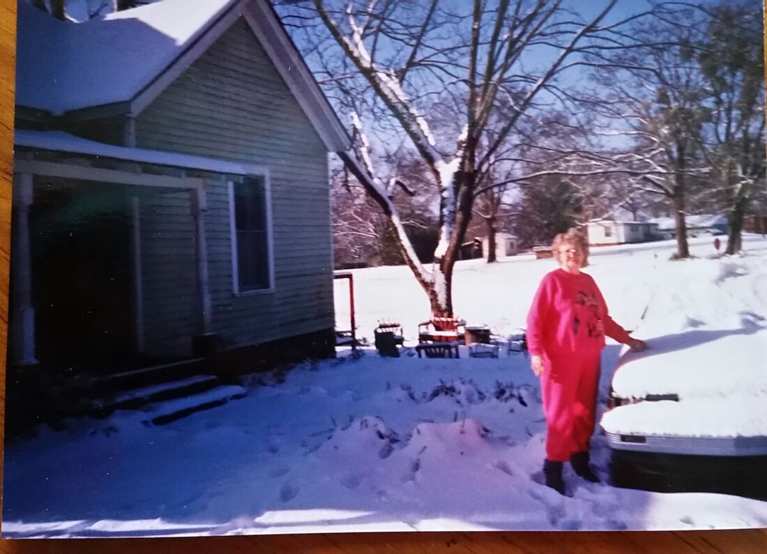 picture of a grandmother standing in front of her snow covered car