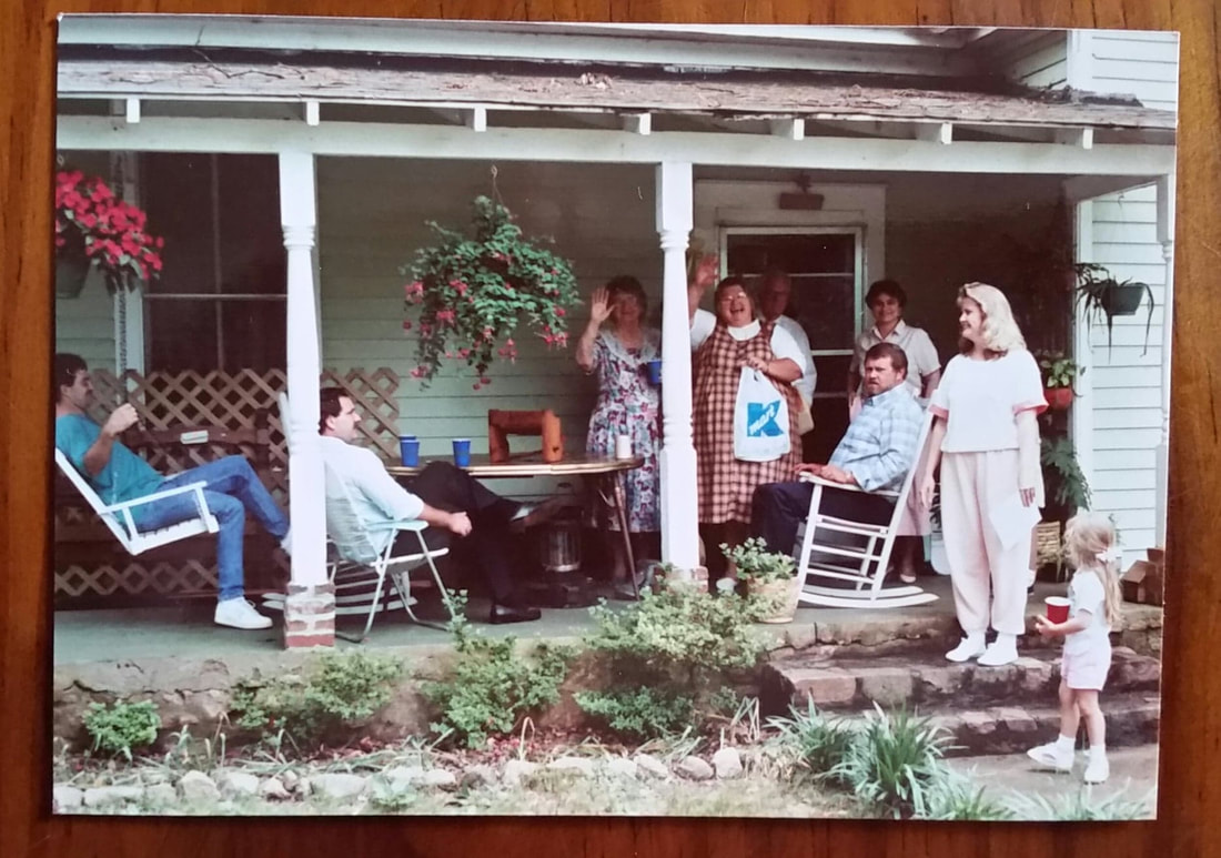 picture of an old picture, family gathered and waving from the front porch