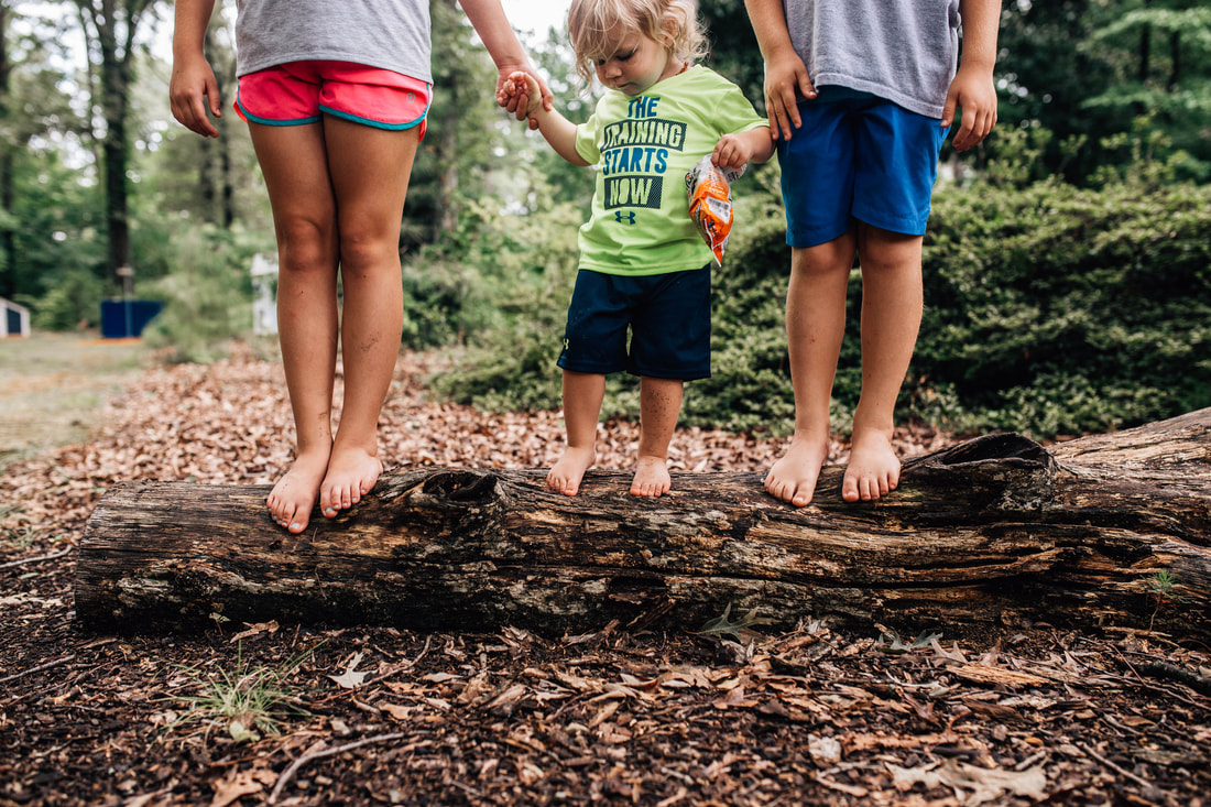 picture of 3 children standing on a log barefoot and holding hands