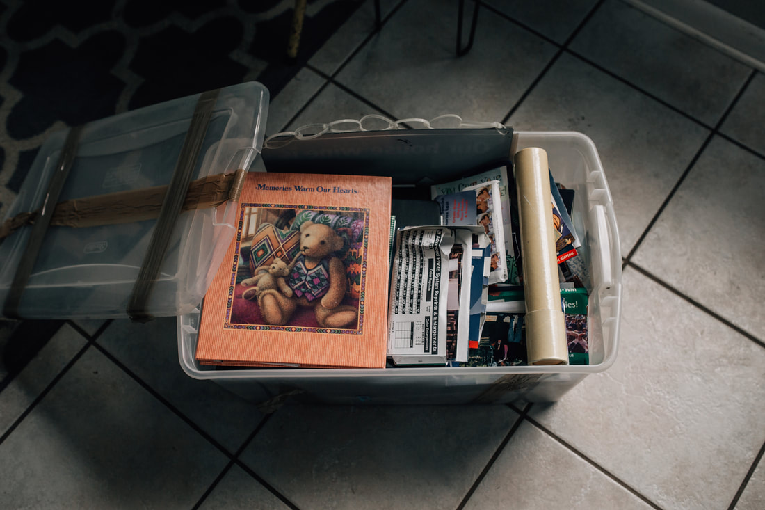 picture of rubbermaid tote filled with books, albums, and old prints and negatives