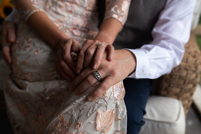 close up details of brides dress and grooms hand resting on her knee with wedding rings