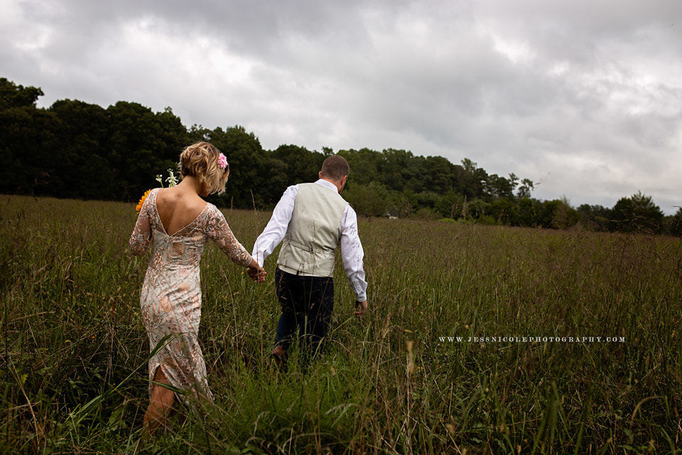 bride and groom walking in field of tall grass