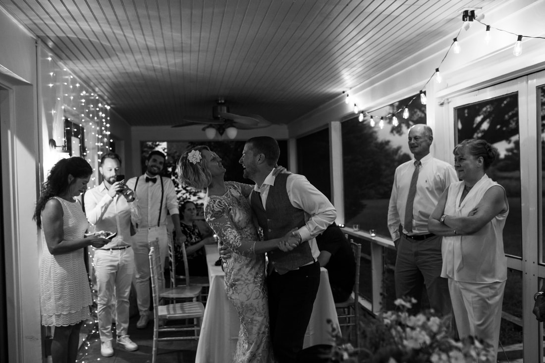 bride and groom share their first dance as husband and wife on the front porch of farmhouse wedding venue