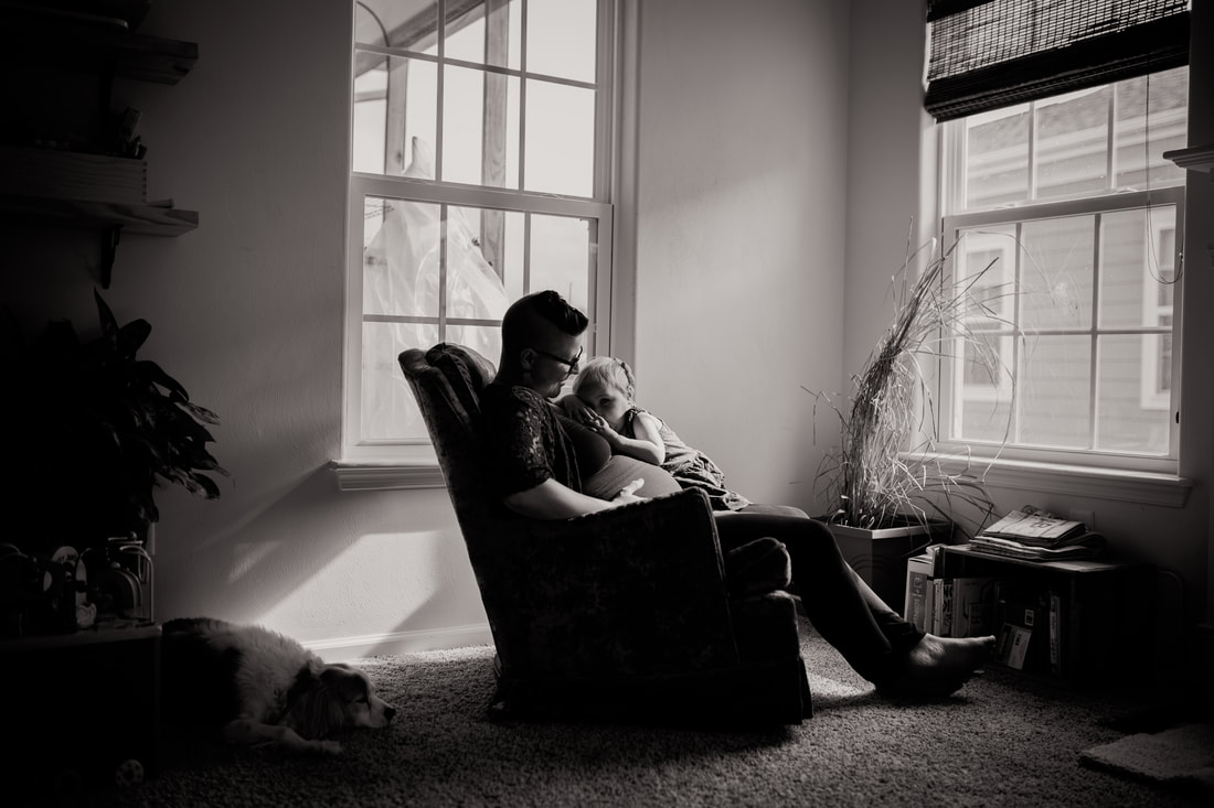 black and white portrait of mother nursing toddler in her home with dog by her side