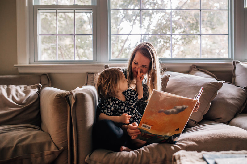 mom and daughter reading book together