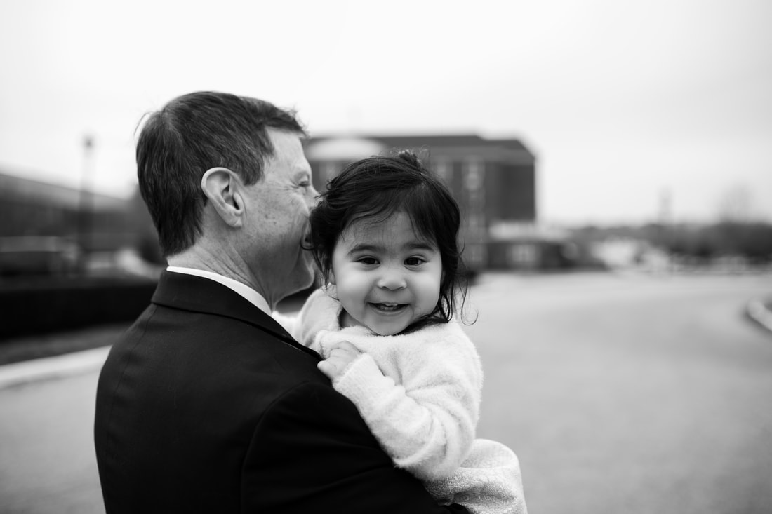 black and white picture of grandfather holding granddaughter at virginia beach courthouse