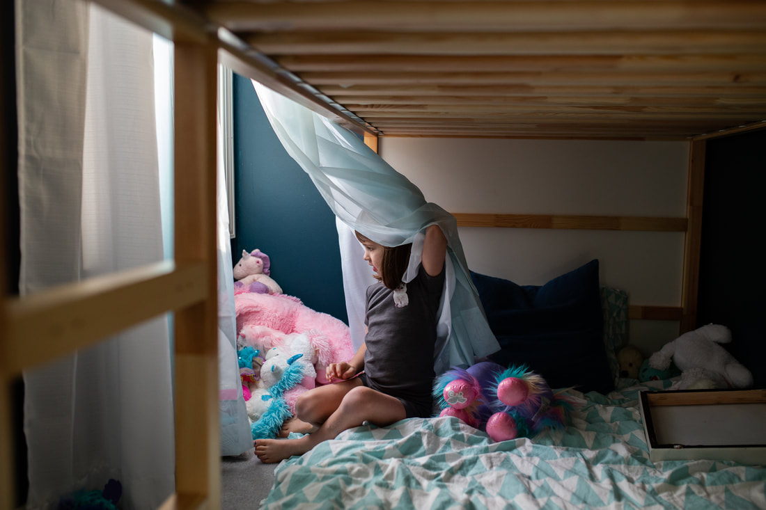 girl on the bottom bunk of bed surrounded by stuffed animals looking out the window
