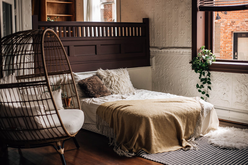 photo of studio with bed and wicker chair with plant in window