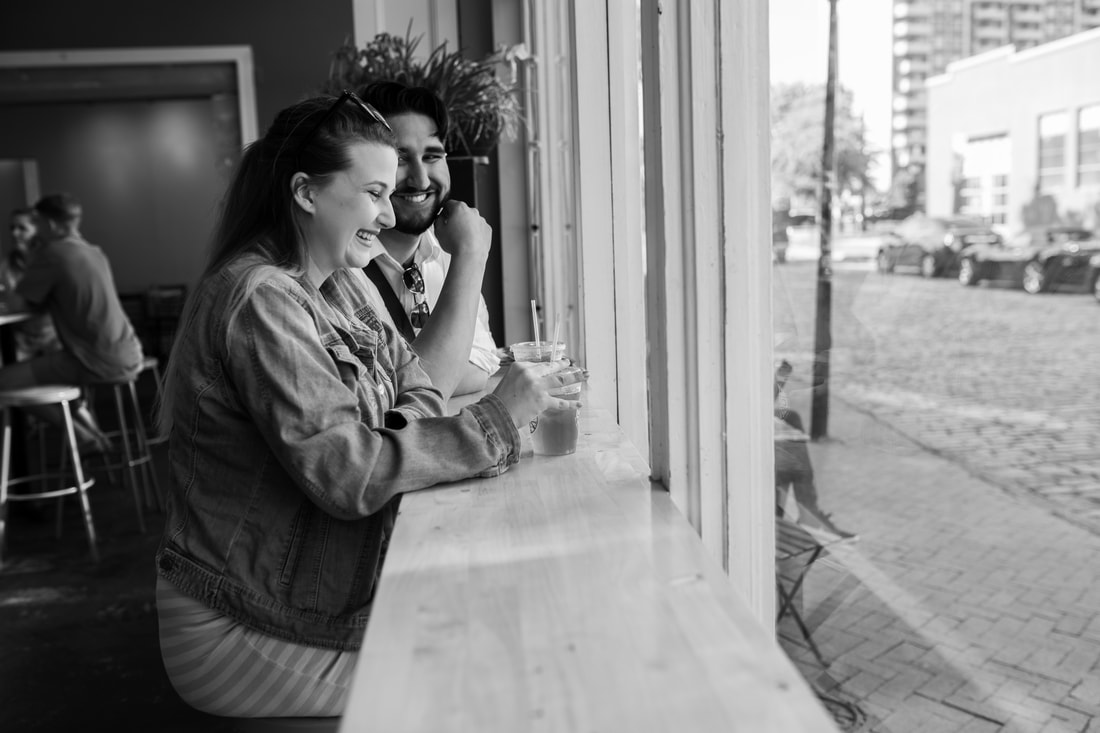 couple sitting at the window bar at the cure coffee house in downtown norfolk virginia