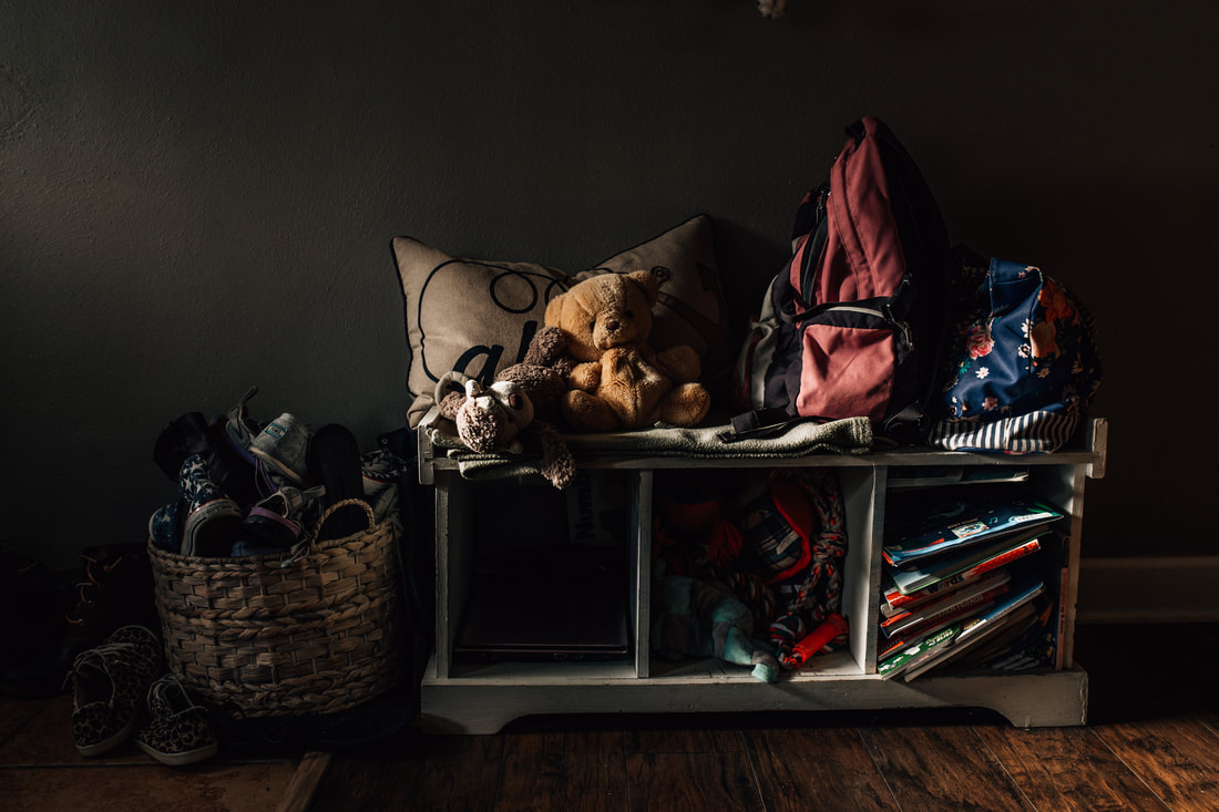 front entryway with shoe basket, bags, dog toys, and books