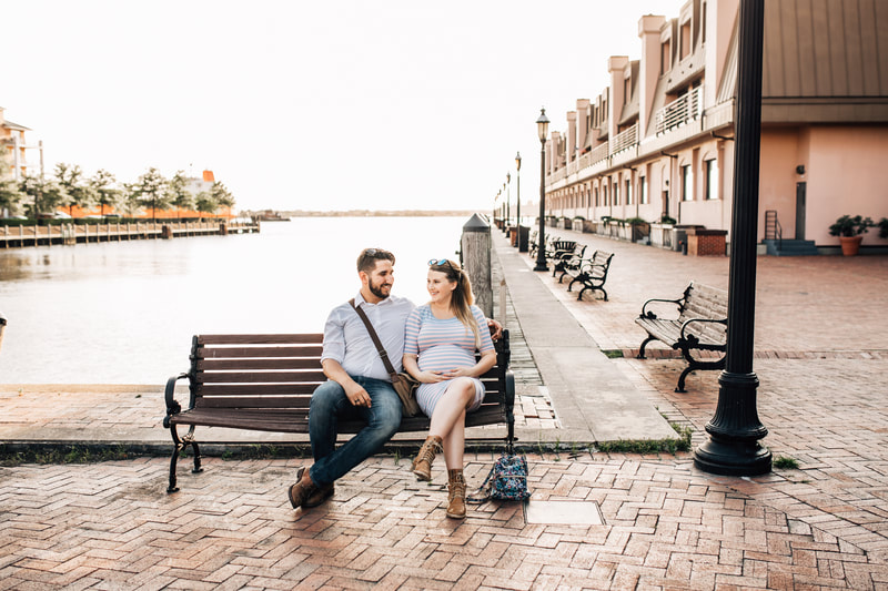 pregnant couple sitting on bench in downtown norfolk beside elizabeth river