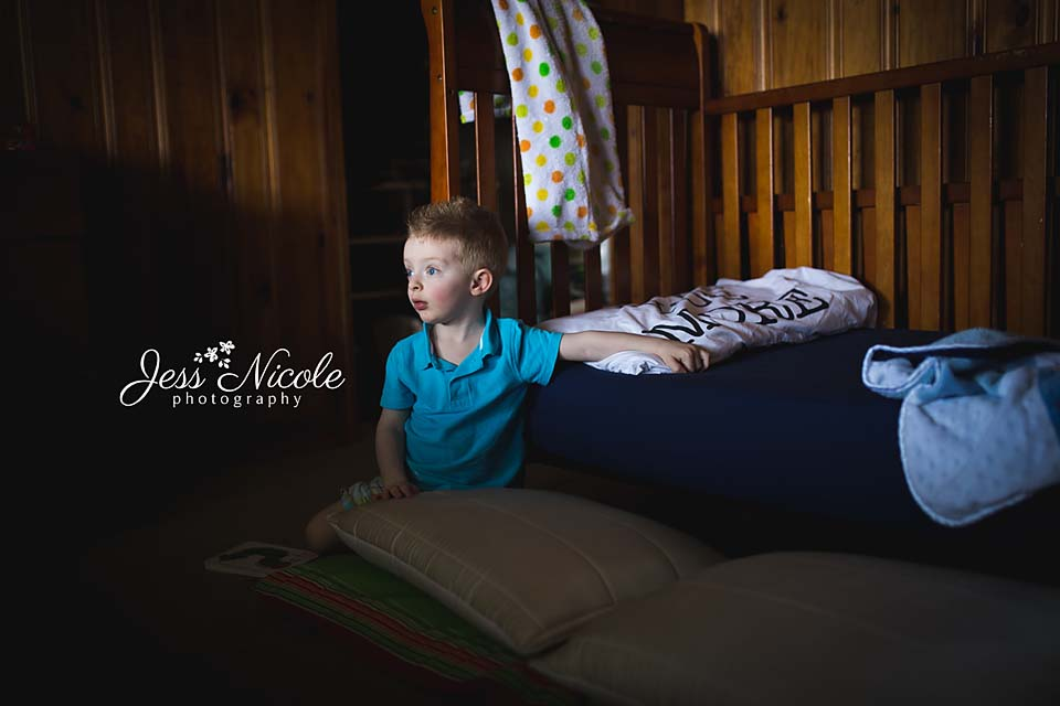 child sitting in front of bed in chesapeake, virginia
