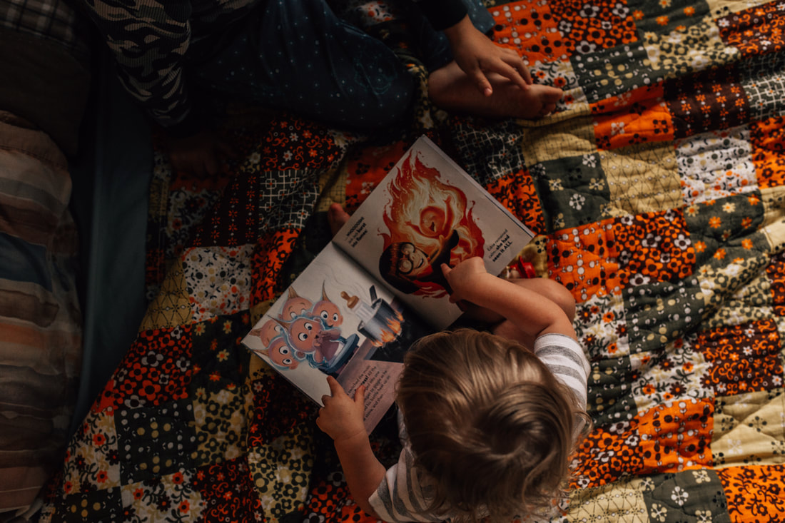toddler sitting on orange colored quilt with incredibles book in his lap pointing at the pictures