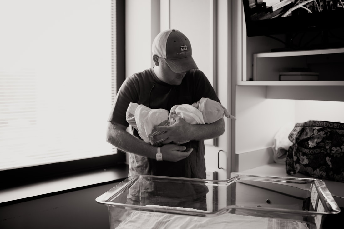 dad holding newborn baby near hospital window with bassinet in the foreground