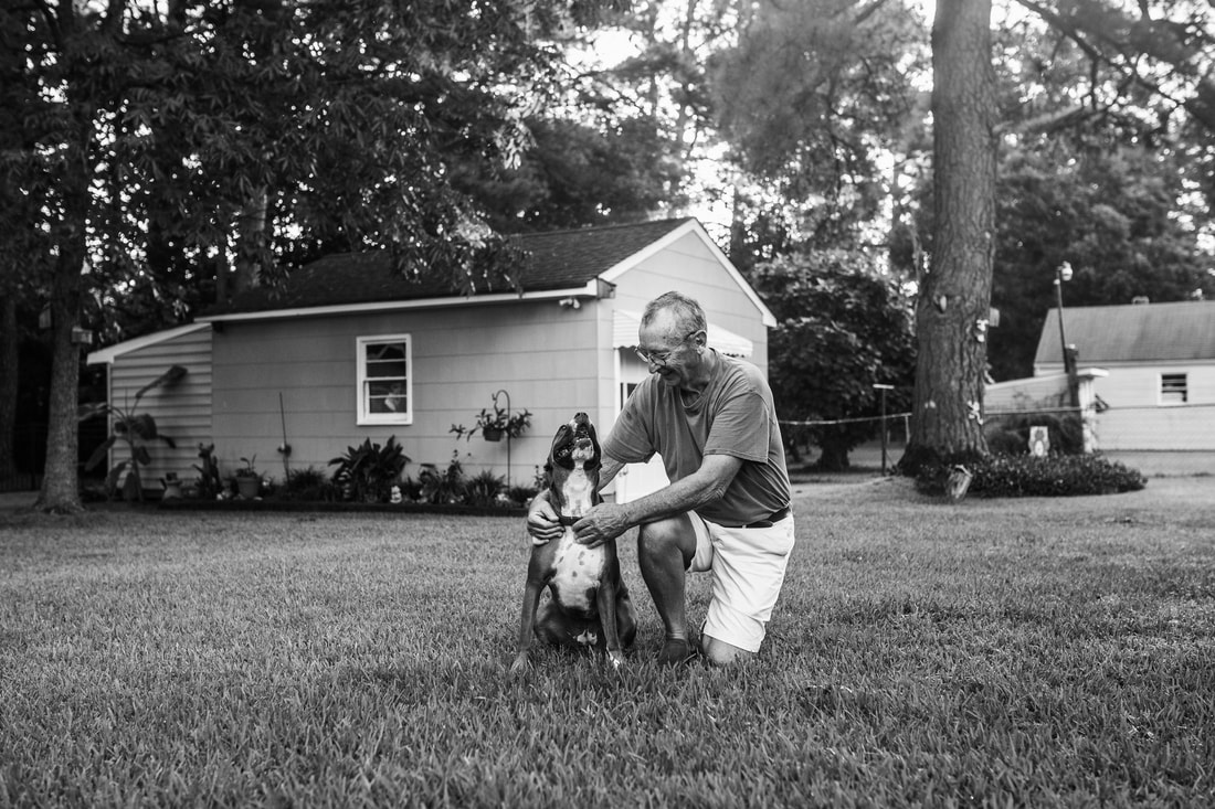 black and white image of boxer dog and owner in backyard smiling at each other