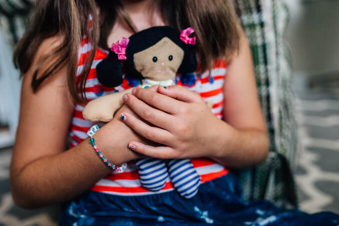girl holding and hugging a stuffed doll